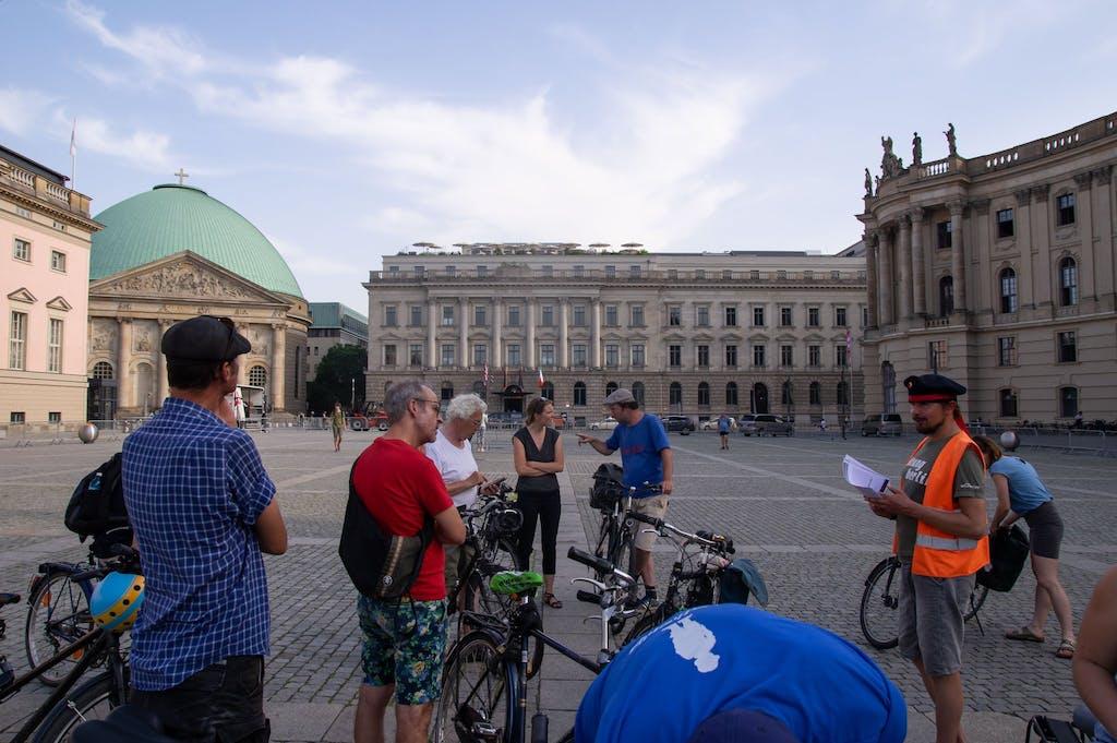 Eine Gruppe von Radfahrern stoppt auf dem Bebelplatz, ein Guide berichtet von sog Novemberrevolution.
