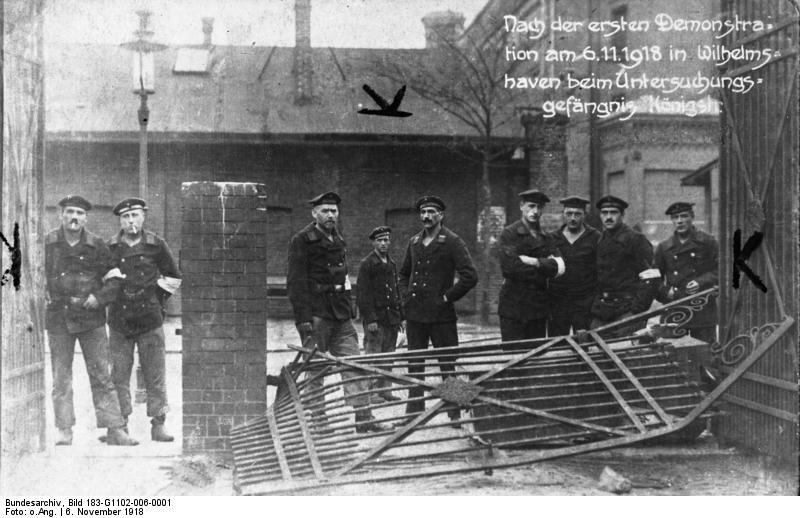 Nach der ersten Demonstration am 6.11.1918 in Wilhelmshaven bei Untersuchungsgefängnis Königstr[aße] Zentralbild, Archiv, 2.11.1968, Zum 50. Jahrestag der Novemberrevolution in Deutschland. Revolutionäre Matrosen an der Spitze der Revolution Am 5. November 1918 hatten Matrosen in Wilhelmshafen den Aufstand vorbereitet. Am 6. November morgens überwältigten sie die Wachen und bewaffneten sich. Über 10.000 Matrosen und Soldaten, denen sich die Werftarbeiter anschlossen, demonstrierten durch die Straßen der Stadt, befreiten ihre gefangenen Kameraden aus den Arrestanstalten (Auf dem Bild: Revolutionäre Matrosen nach der Erstürmung des Gefängnisses in der Königsstraße) und forderten die Errichtung einer sozialistischen Räterepublik. (am 6.11.1918)