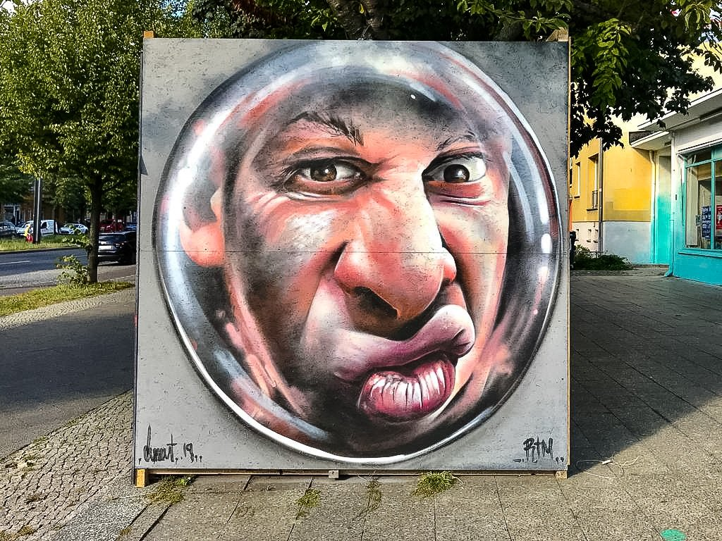 a close up of a mans face painted on the side of the street