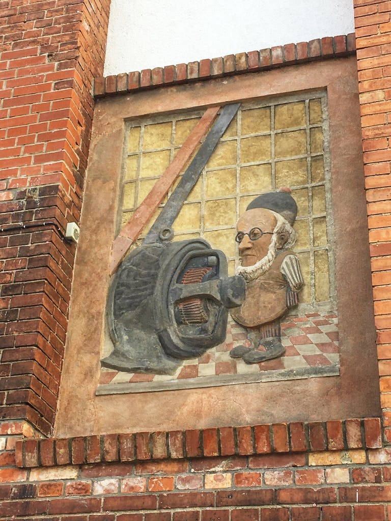 Dieses Relief an der Fassade des Motorwerks soll den Maler Adolph von Menzel darstellen, der als Maler Preußens bekannt wurde.
