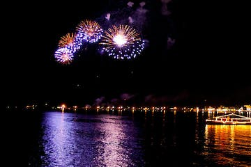 fireworks in the night sky over a body of water