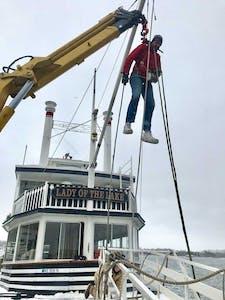 crew member on a crane doing maintenance
