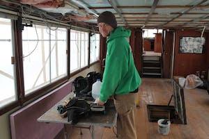 crew member performing off-season maintenance on boat