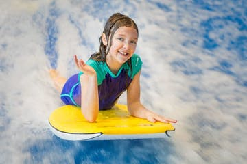 a young girl riding a wave on a surf board