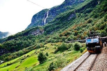 a train traveling down train tracks near a mountain