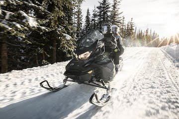 a man riding a motorcycle down a snow covered slope