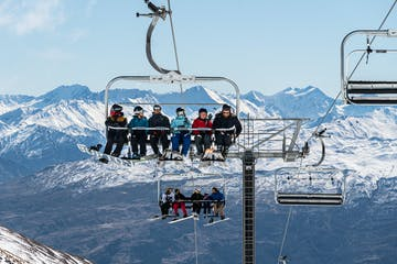 a group of people riding skis on top of a snow covered mountain