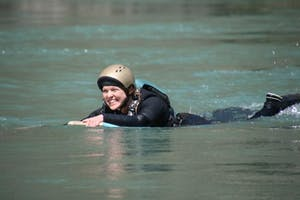 a girl riding a wave on top of a body of water