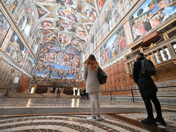 a person standing in front of Sistine Chapel
