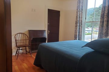 a bedroom with a bed and a chair in a room