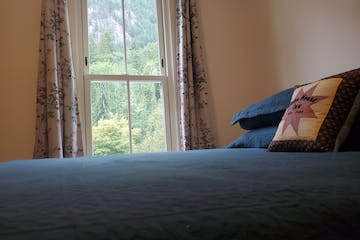 a made bed in a bedroom next to a window