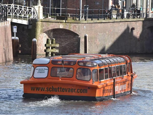 a bus is traveling down the water in front of a building