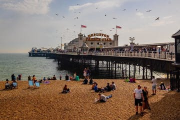 a group of people sitting at a beach with Brighton Pier Rock Shop in the background