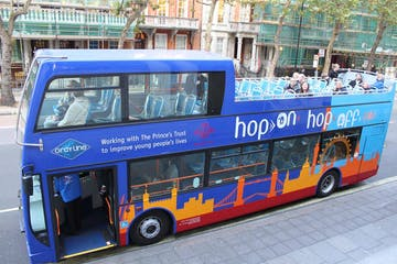 a blue double decker bus driving down a street