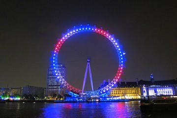 a large bridge lit up at night with London Eye in the background