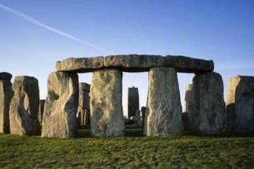 a large stone building with Stonehenge in the background