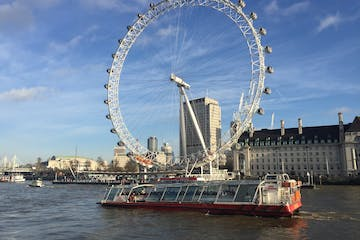 a large ship in a body of water with London Eye in the background