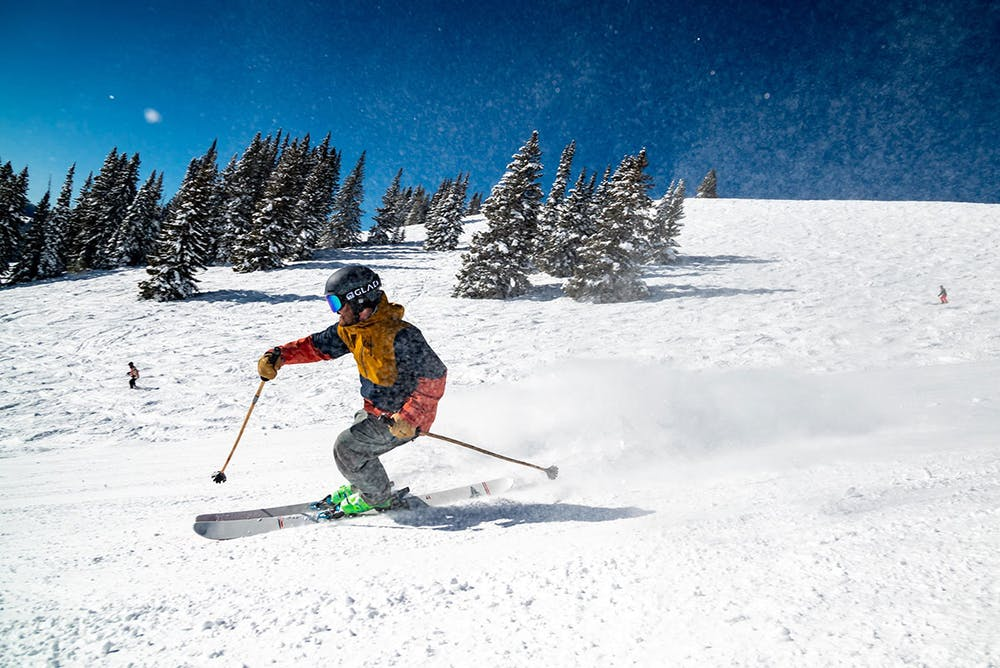 a man skiing down a snow covered slope