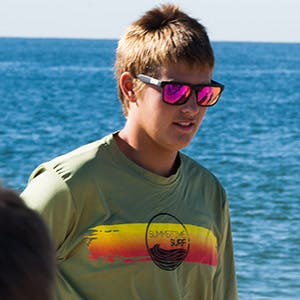 a person wearing sunglasses and a body of water