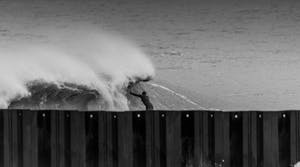 a person riding a wave on top of a wooden fence