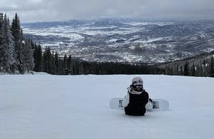 a man sitting on top of a snow covered slope