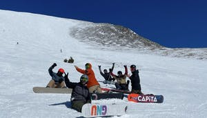 a group of people sitting on a snow board