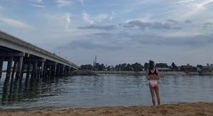 a person standing next to a body of water