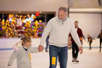 father and daughter ice skating together