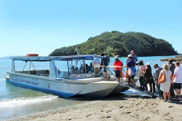 a group of people boarding the glass bottom boat
