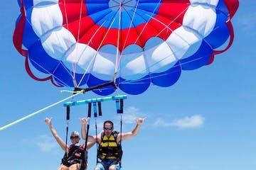 a person flying through the air on a parachute