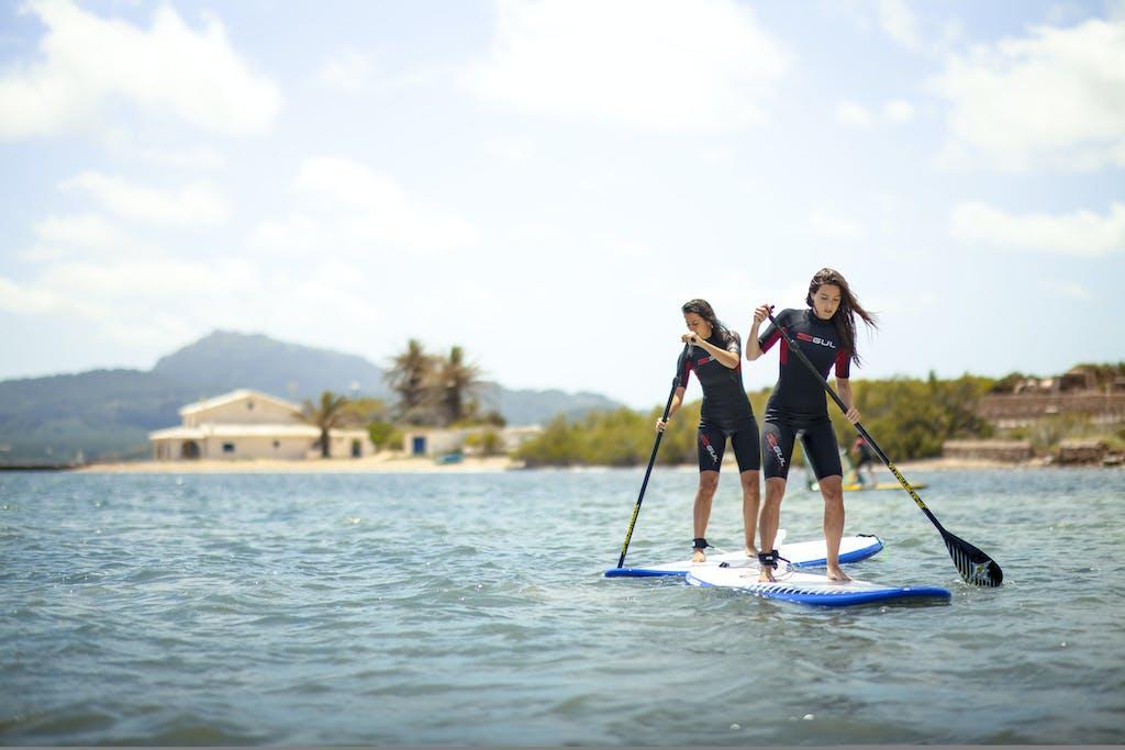 2 chichas haciendo paddle surf en Fornells