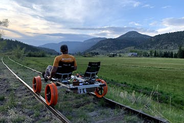 a man sitting on a train track with a mountain in the background