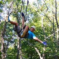 A guest zipping through the ropes course.
