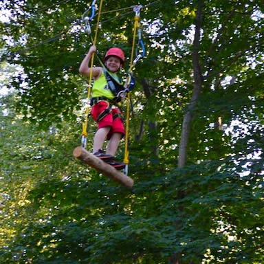 A guest swinging on the ropes course.