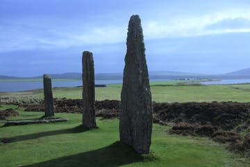 a large green field with trees in the background with Ring of Brodgar in the background