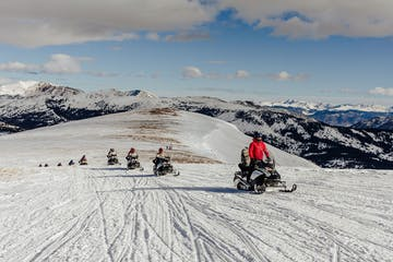 a group of people riding skis down a snow covered slope