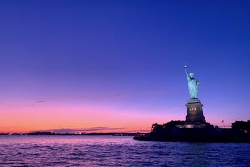 Statue of Liberty with purple sunset sky during private sail in NYC
