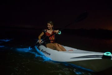 a woman paddling a kayak in bioluminescent water