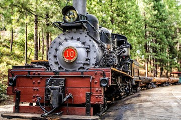 a steam engine is sitting on a train track