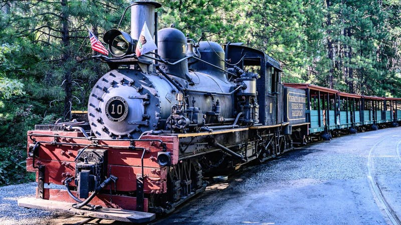 a steam engine train traveling down train tracks