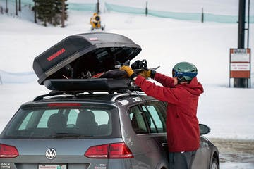 a person riding a snowboard down a snow covered car in a parking lot