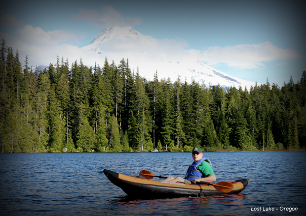 a man riding on the back of a boat next to a forest