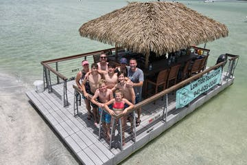 a group of people sitting on a dock next to a body of water