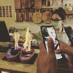 chorizo being grilled waitress with mask protection
