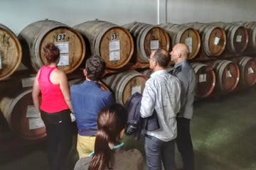a group of people standing in front of a barrel