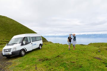 a man in a green car on a grassy hill