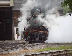 a steam engine on a train track with smoke coming out of it