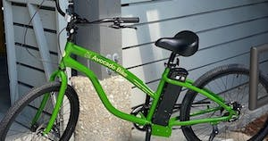 a bicycle parked in front of a green pole