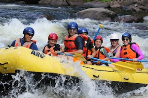 a group of people riding on a raft in the water