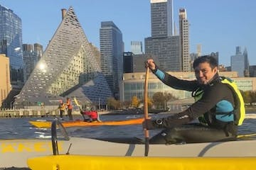 a man riding an outrigger canoe in front of the VIA Building in Manhattan on the Hudson River